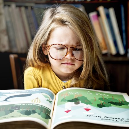 Cute and adorable little girl with glasses getting stressed out as she is reading