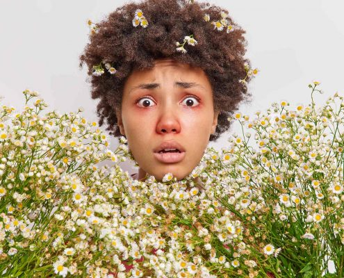 woman-surrounded-by-camomile-has-allergic-reaction-wildflowers-stares-has-red-swollen-eyes-poses-white